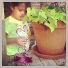 young girl outside next to plant