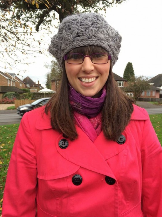 A photo of Sophie Webster outdoors wearing a red coat and gray knit hat