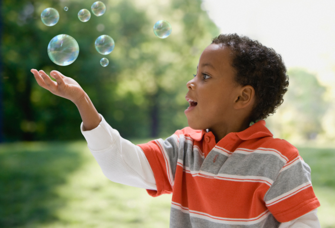 boy catching bubbles outside