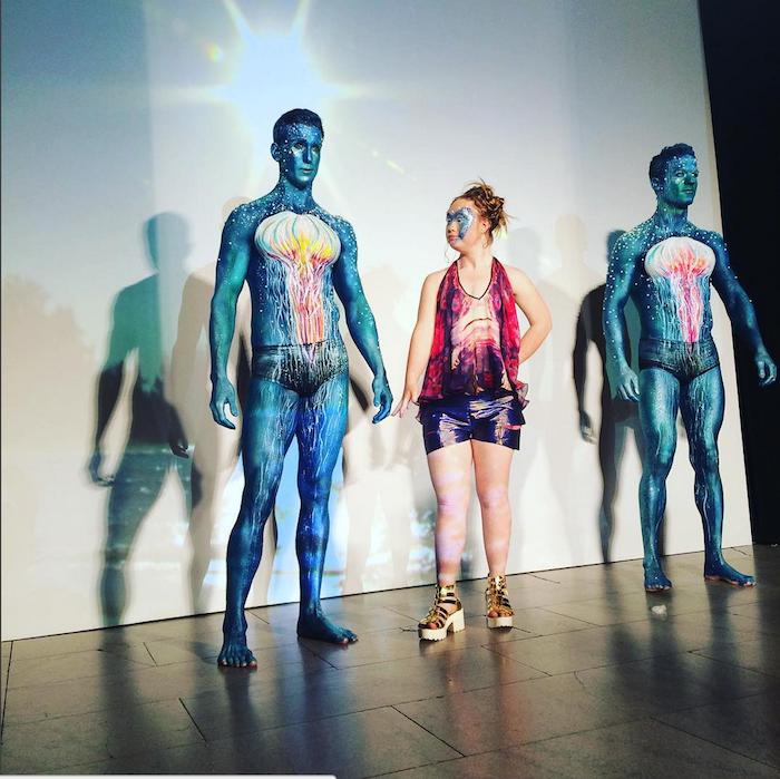 Madeline Stuart next to two men at FTL Moda 2015 NYFW show