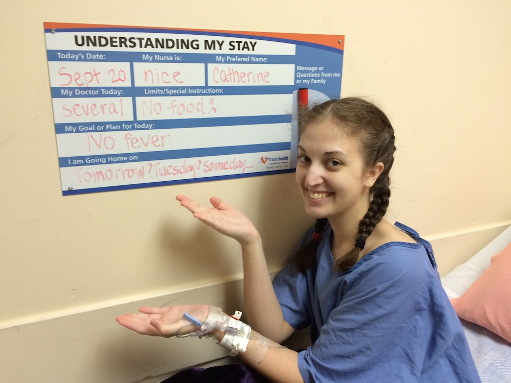 a woman in a hospital displaying a medical chart with her information