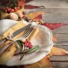 Autumn rustic table setting with berries, leaves, acorns and nuts