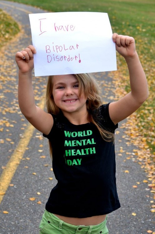 """Jade's daughter is smiling and holding a sign that says, """"I have bipolar disorder!"""" She has blonde hair, and is wearing a black shirt that says """"World Mental Health Day"""" in green."""