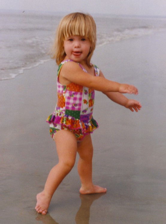 little blonde girl at beach in bathing suit