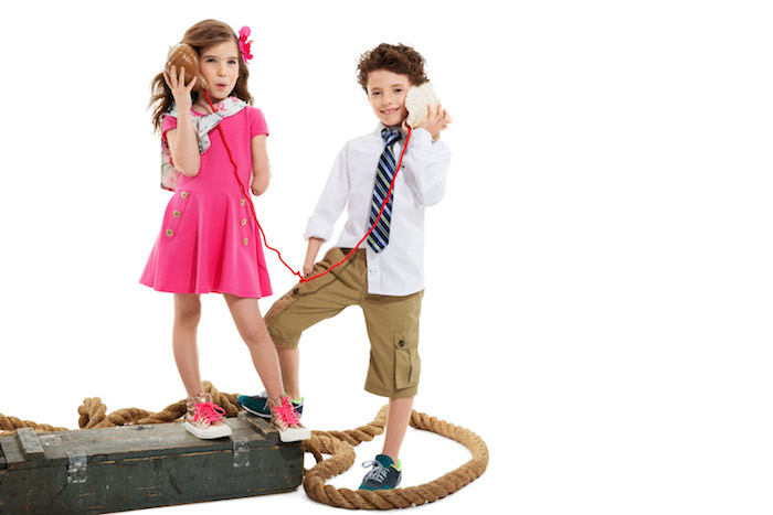 Two children, one with a limb difference, wearing adaptable clothing