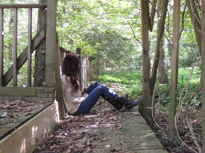 Woman sitting on the ground in a park outdoors