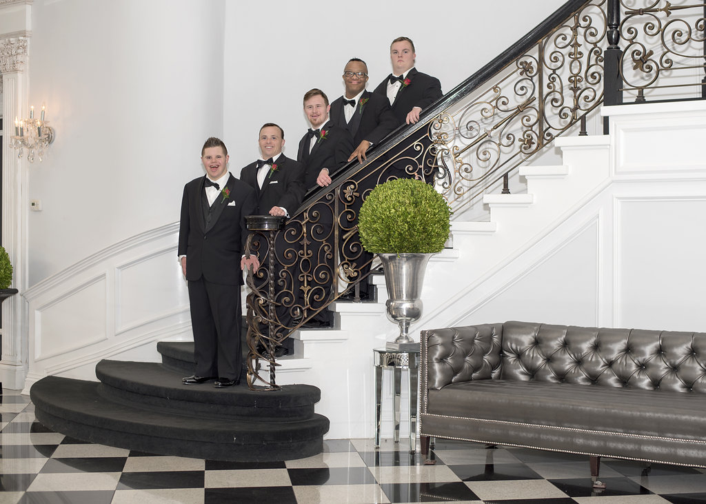 group of young men standing on staircase in tuxes