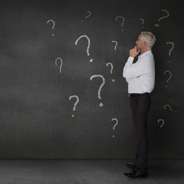 man looking at wall of question marks