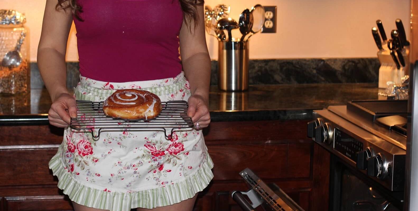 woman holding cinnamon bun