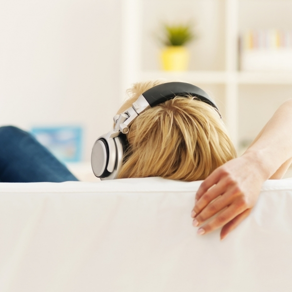 woman sitting on couch with headphones on