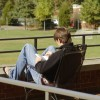 Young man reading on a deck at a college