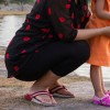 mother crouched down with young daughter at water edge