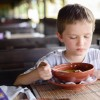 7 years old child, boy eating soup in restaurant