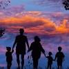 Silhouette of family against sunset sky