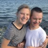 A young woman stands next to her brother with Down syndrome in front of body of water