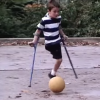 A small boy with an amputated leg and on crutches kicks a soccer leg