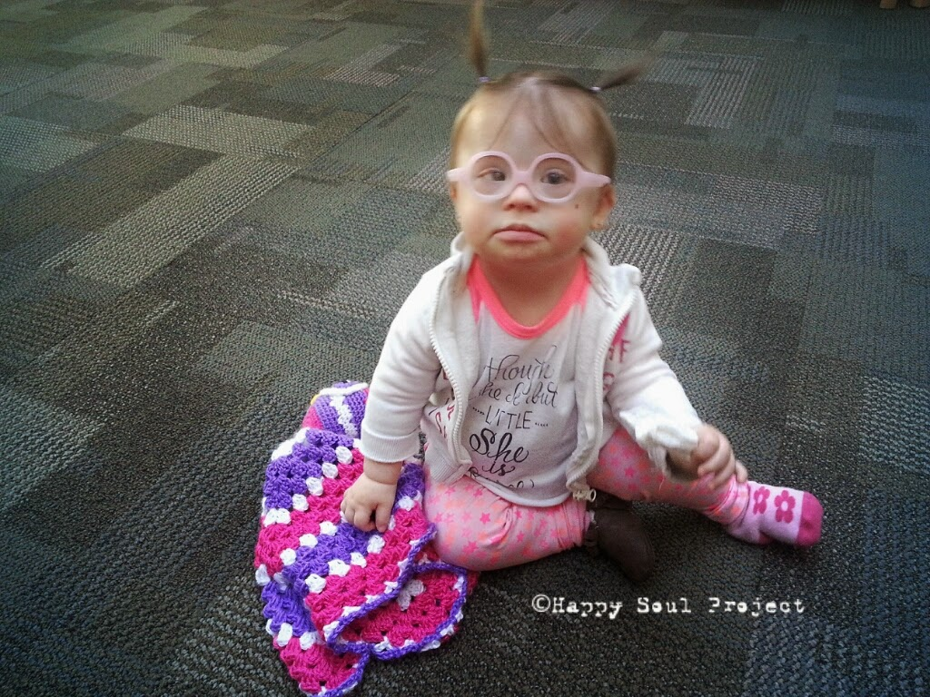 baby with down syndrome sitting on the floor