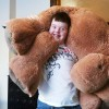 Boy stands with life-size teddy bear over his head