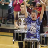 A boy, with his drum sticks raised in the air, leads the drum line in pep rally