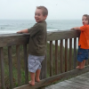 two boys standing on railing overlooking the beach