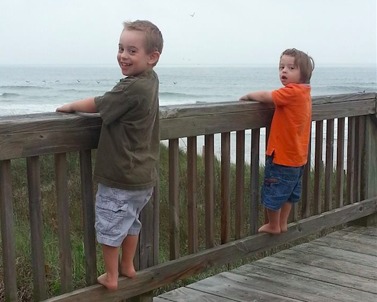 two boys standing on a railing overlooking the beach