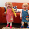 Two twin small girls standing in front of a couch