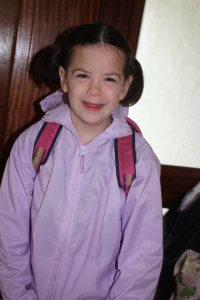 Little girl wearing a backpack and smiling.