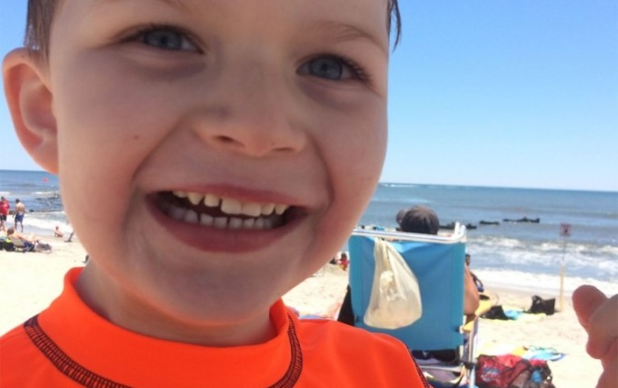 young boy in bright orange shirt smiling on the beach