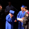 A boy walks across stage in cap and gown with twin brother