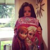 """A little girl holding her """"Frozen"""" theme back pack up to her face with the characters Anna and Elsa from the movie on the front of the backpack"""