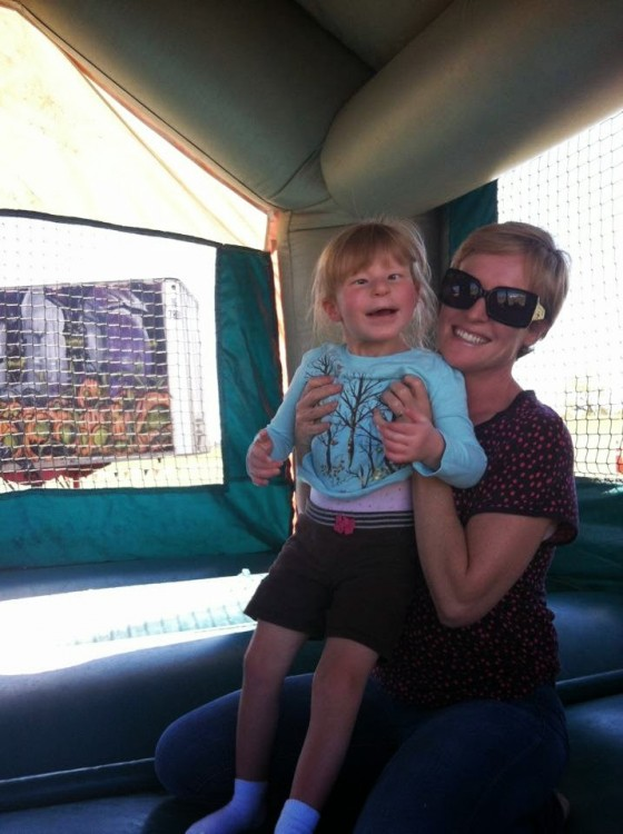 mom holding daughter inside bounce house