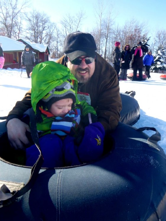 father and his young son tubing in the snow