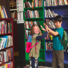 kids holding hands in front of bookshelves