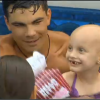 A small, bald girl with cancer in a swimsuit and floaters, as she smiles in a pool with a man swimming behind her