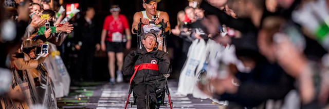 A man pushing his twin brother in a wheelchair to finish line of race