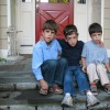 Three borther sit on the steps in front of a door