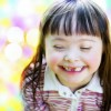 An uplcose photo of a girl with Down syndrome smiling