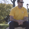 Green Bay Packers player, Aaron Rodgers, sitting with a young girl on the grass