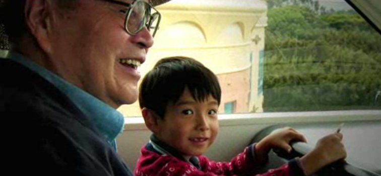 A gradnfather smiling as he sits next to his grandson