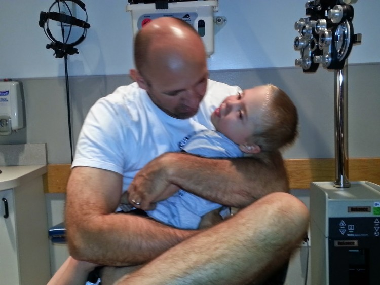a father holding his son in his arms at the doctors office