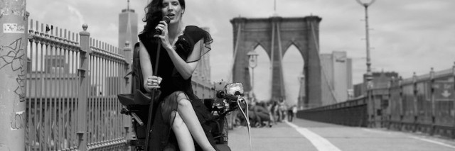 photograph of woman in motorized wheelchair with service dog on a bridge