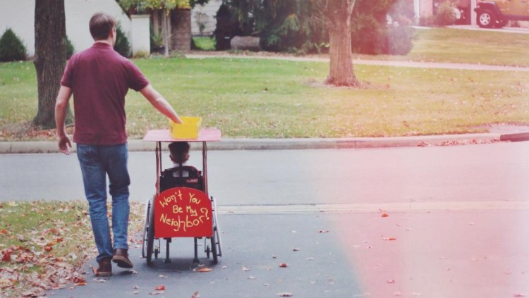 father pushes around boy in his mister rogers costume