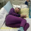 A young girl curled up in a hospital bed with bandages on her head.