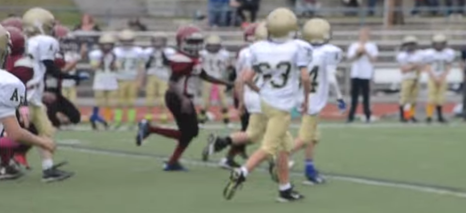 A football play as one player runs to make a touchdown and the opponent players run alongside him