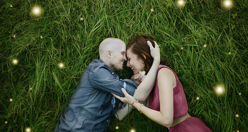 A couple touching heads together as they lie on grass