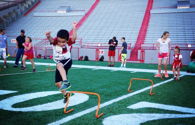 Boy with autism jumping over hurdles on a football field