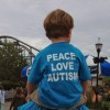 "A small child sitting on parents' shoulders and they are both wearing t-shirts that say, ""Peace, Love, Autism"" on the backs"