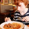 Image of boy eating spaghetti meatballs pasta in Italian restaurant