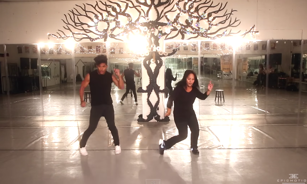 Adult son and mother dance in black costumes