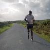 veteran ben mcbean runs down a road next to a grassy field